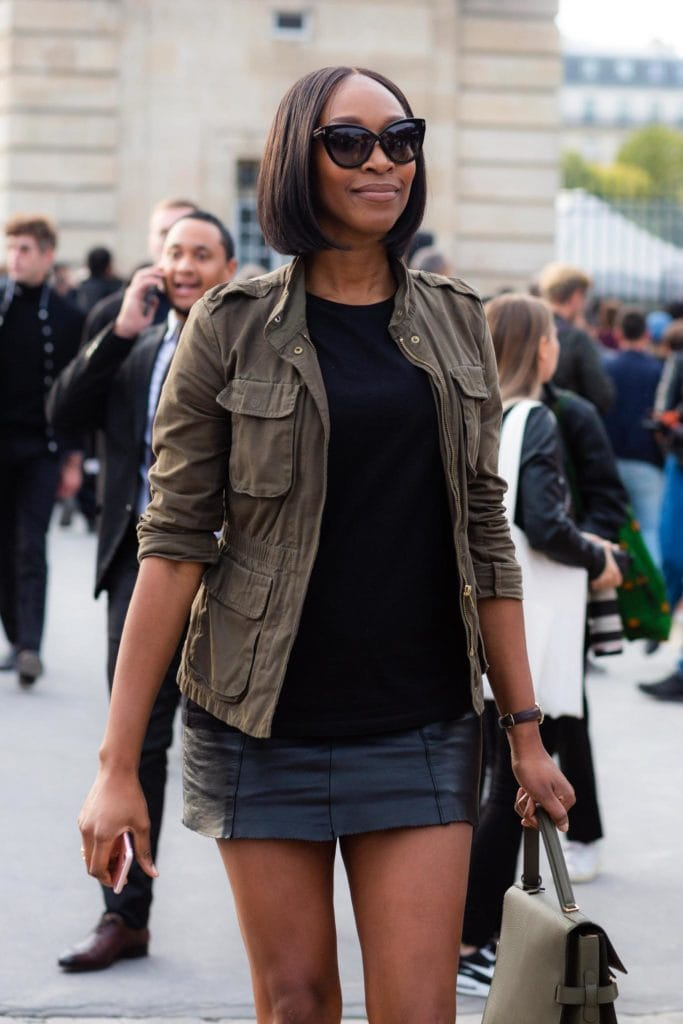 Short hairstyles for fine hair: Woman with dark brown straight hair styled in a sharp bob wearing a utility jacket and mini skirt.