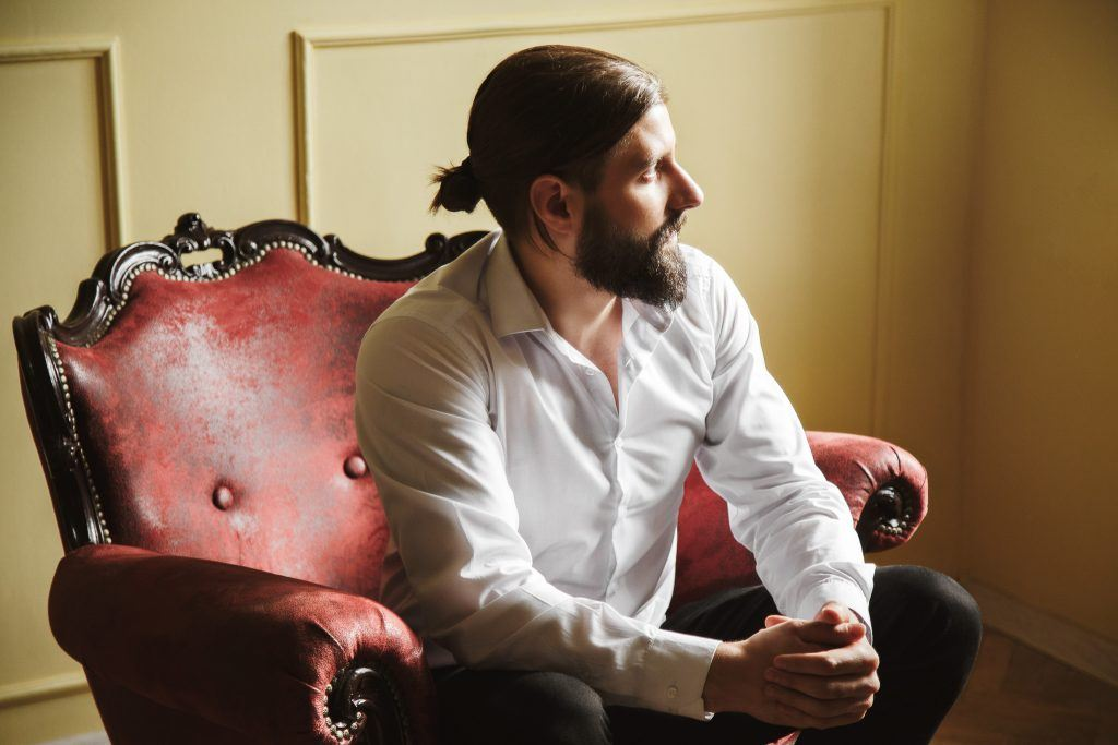 man sitting down with long hair man bun full beard