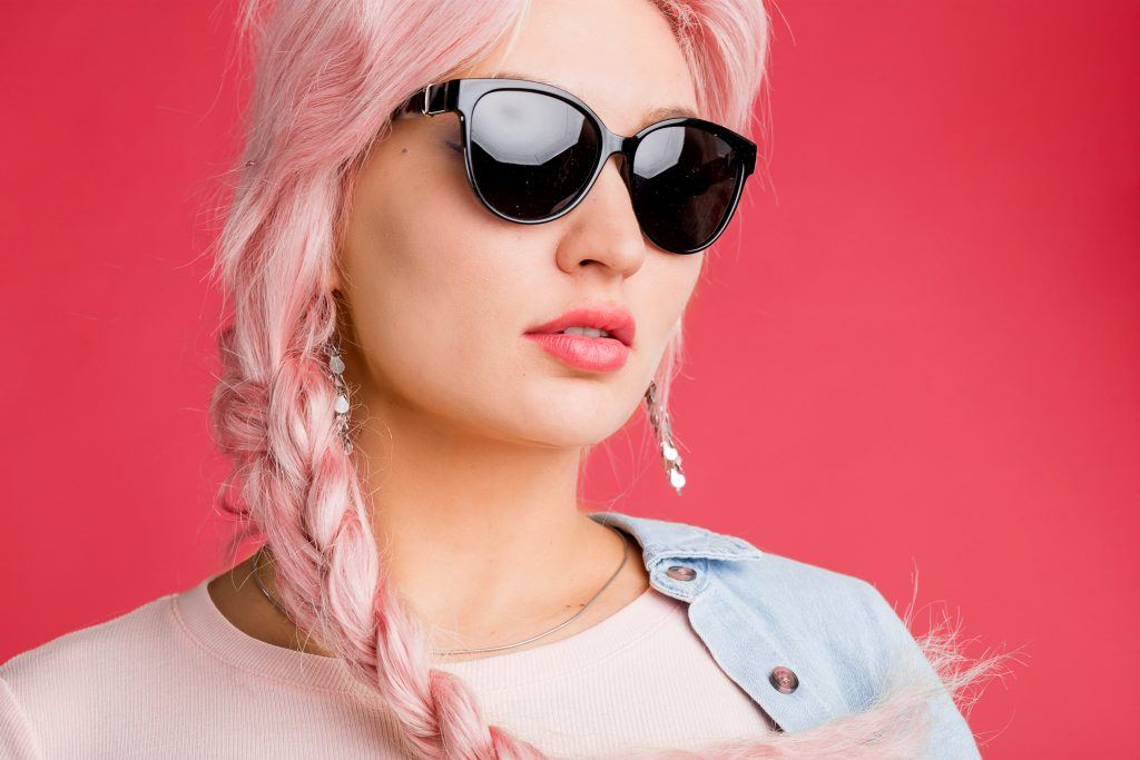 woman with dark sunglasses and pastel pink plait braid