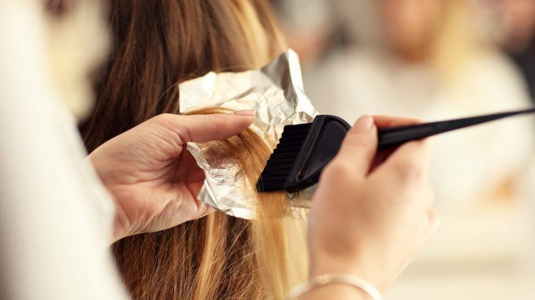 closeup of woman getting her hair dyed professional foils on hair