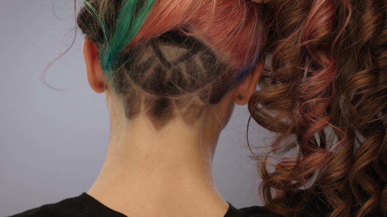woman with long brown curly hair with colourful strands and a fancy undercut