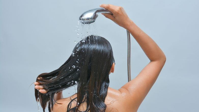 woman with wet hair and shower head