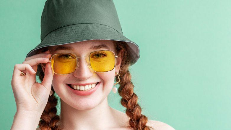 hair accessories: Happy smiling fashionable woman wearing yellow square sunglasses