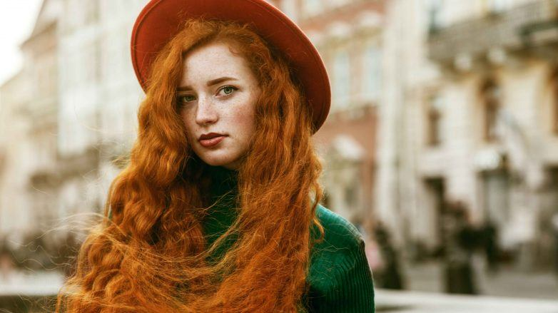 woman with long wavy red hair wearing a hat