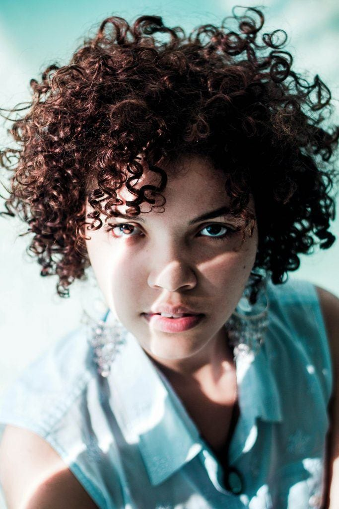 woman with a short, brown curly hairstyle