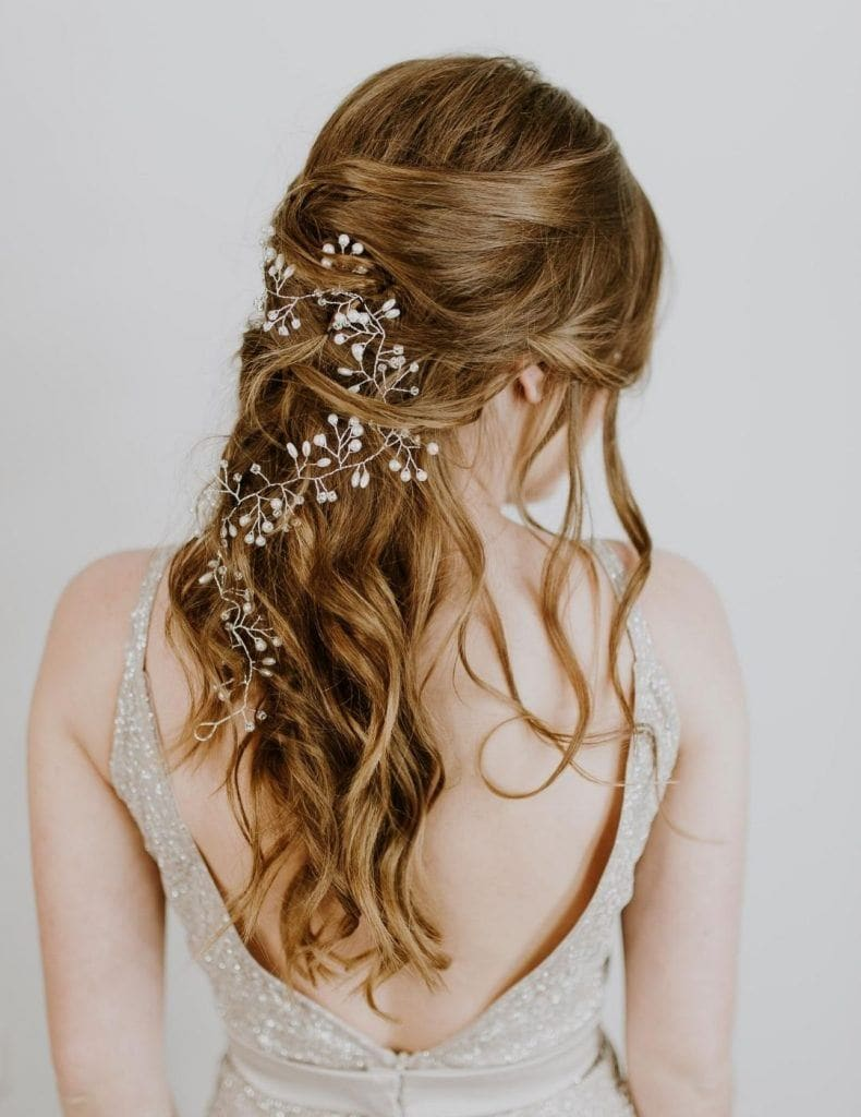 woman with wavy brown hair and shiny accessory looped through