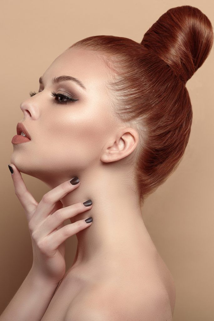 woman with red hair and a sleek high bun hairstyle