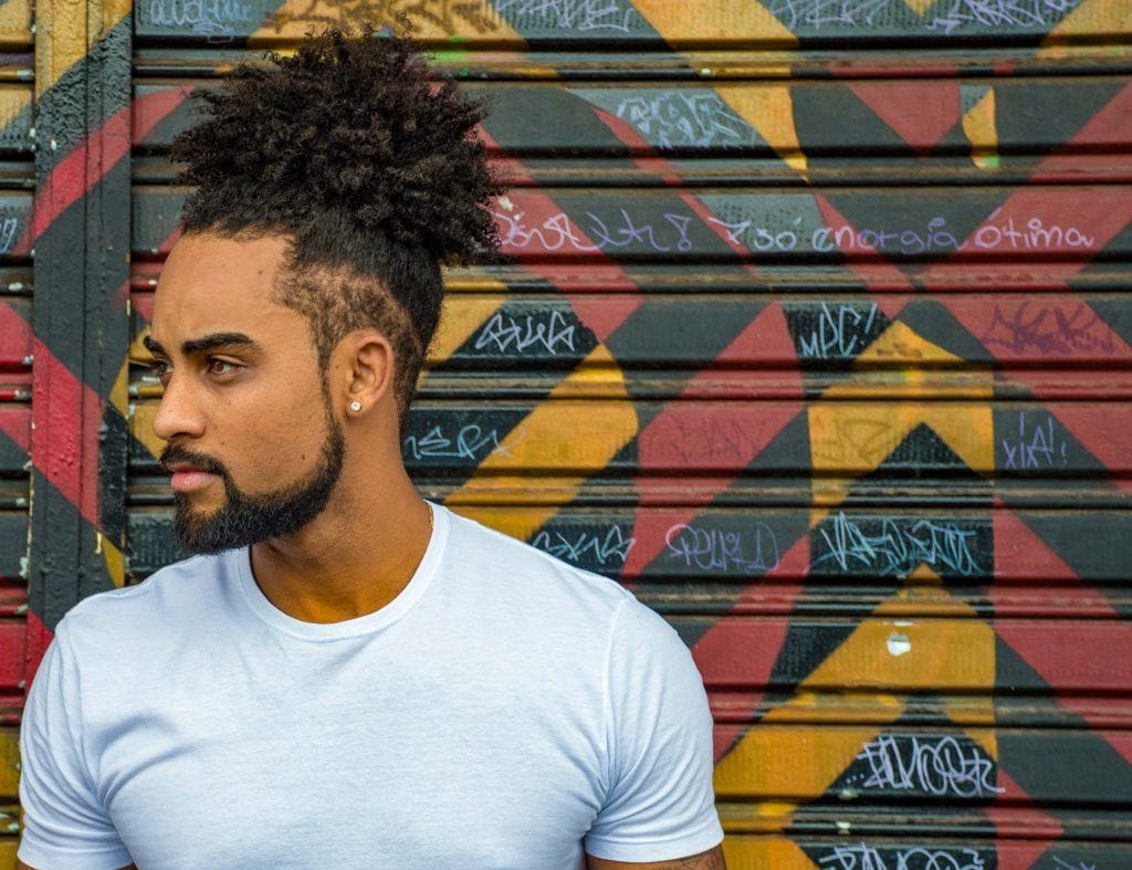 Man with a curly ponytail and slick undercut