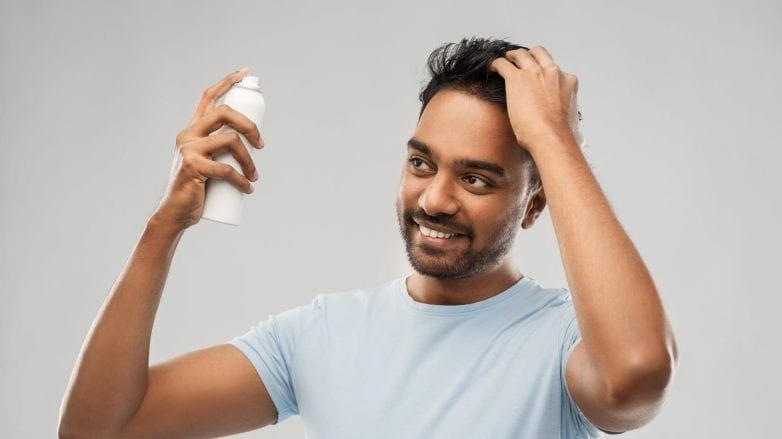 man applying product to his hair