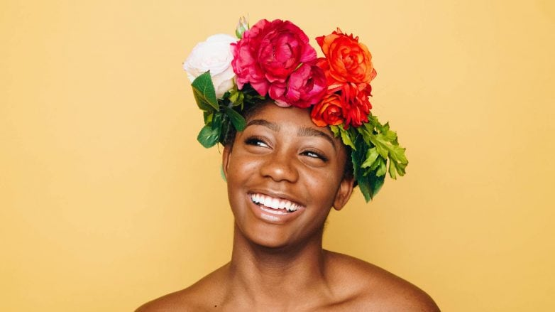 woman wearing a big flower crown accessory, with white and red flowers
