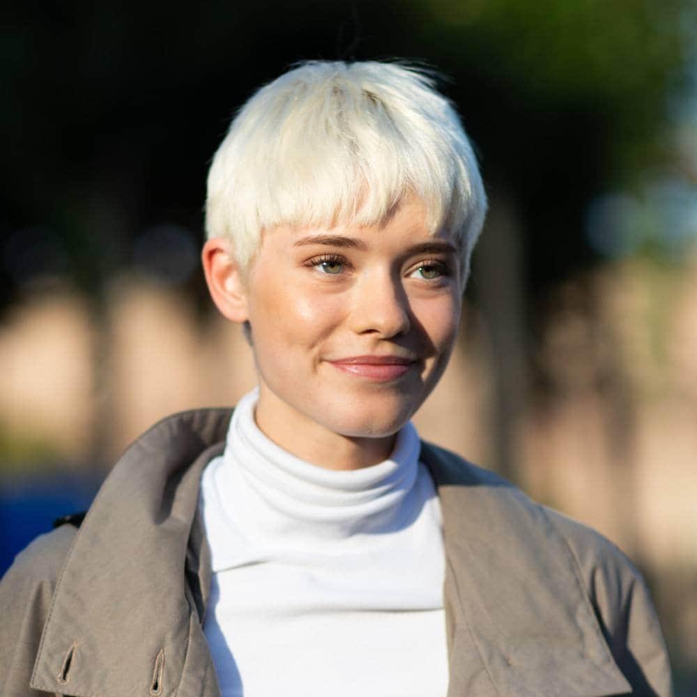 Mujer rubia con corte de cabello pixie con fleco asimétrico