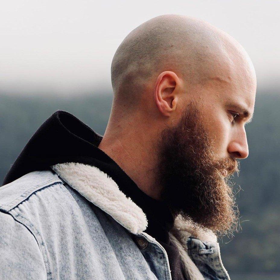Hombre con cabeza afeitada y barba larga tupida