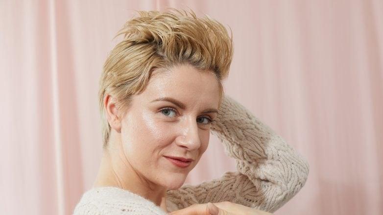 Mujer rubia luciendo peinado mohawk para corte pixie