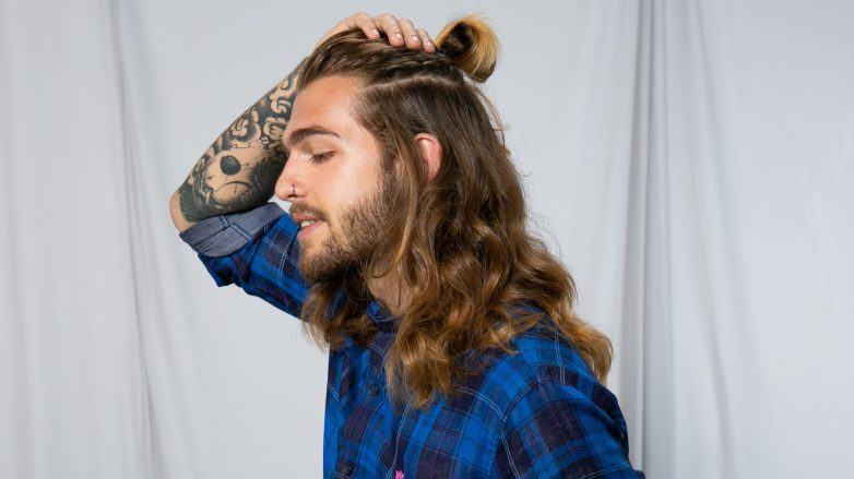 Hombre con cabello largo, medio chongo, trenza y barba