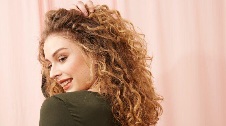 Mujer rubia con cabello rizado definido