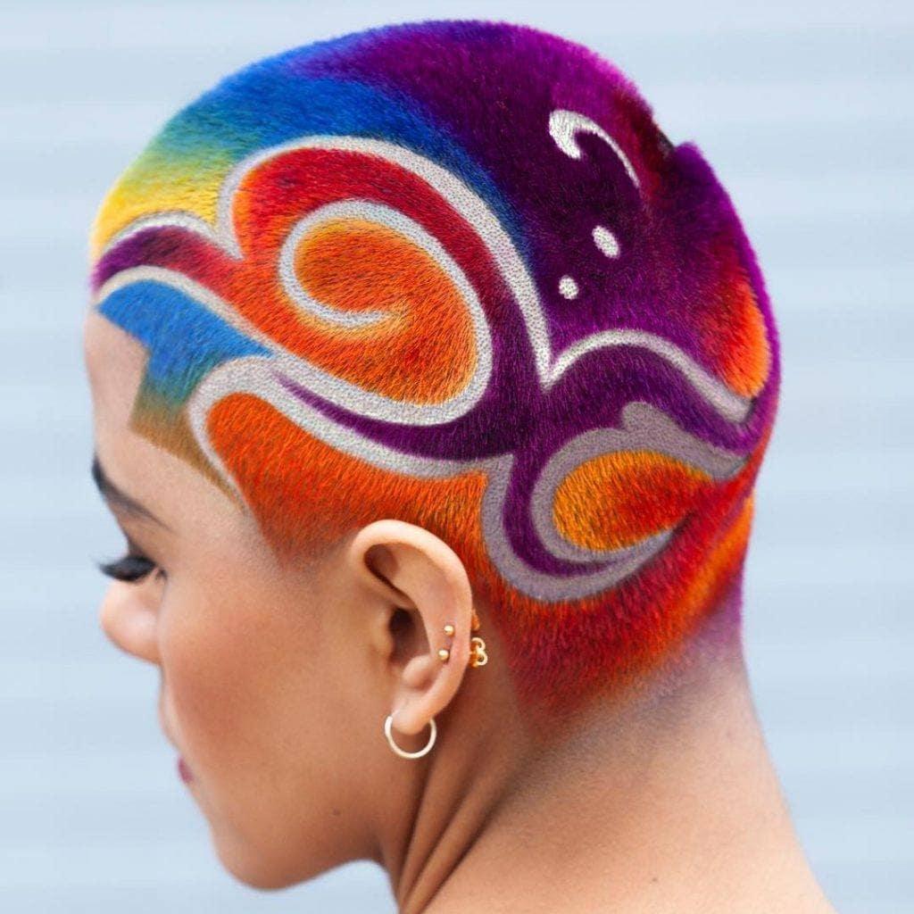 Mujer rapada con grecas en el cabello y tinte arcoíris