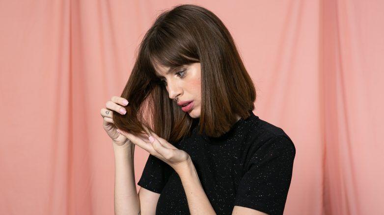 Mujer preocupada observando su cabello