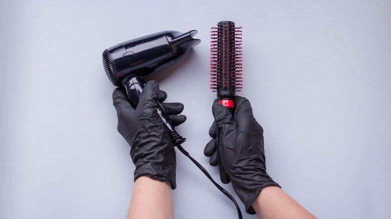 Manos con guantes de látex sosteniendo una secadora y un cepillo redondo