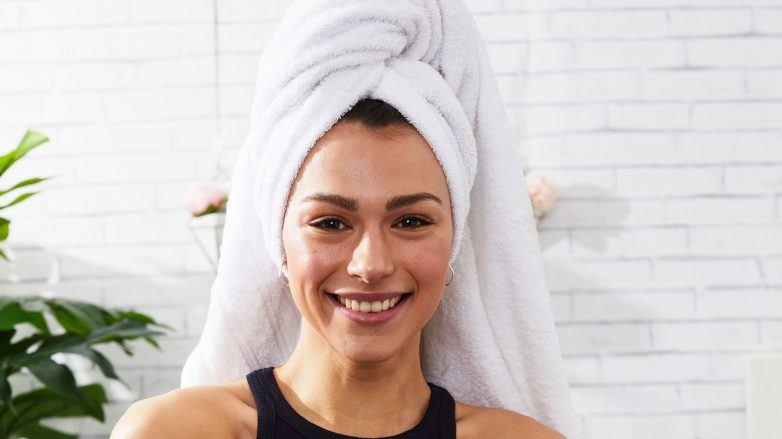 Mujer sonriente con toalla en la cabeza