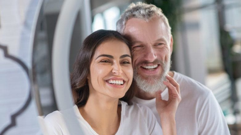 Hombre y mujer con camisetas blancas y sonrientes frente al espejo