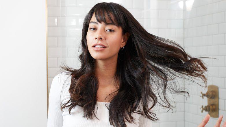 Mujer con cabello negro, largo y con fleco en el baño