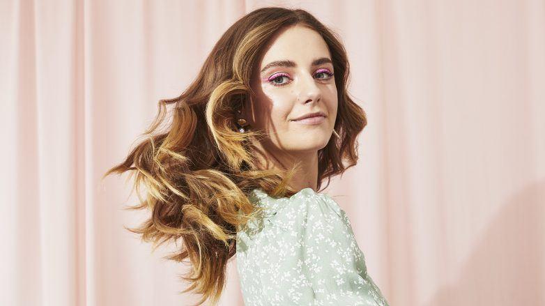 Mujer con cabello rubio, largo y ondulado