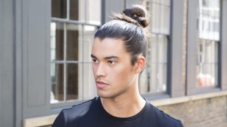 Hombre joven con playera negra y peinado de Samurai en la calle