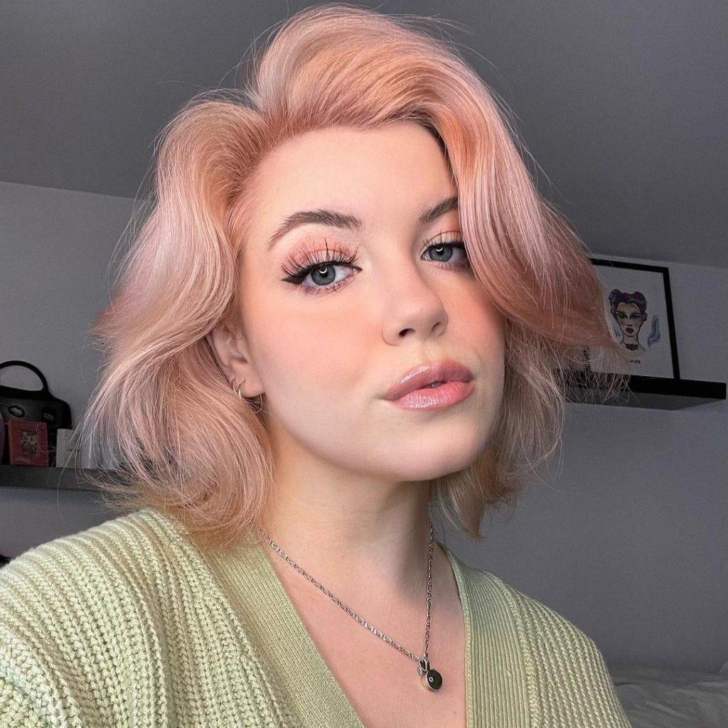 Mujer con cabello rose gold corto con fleco cortina