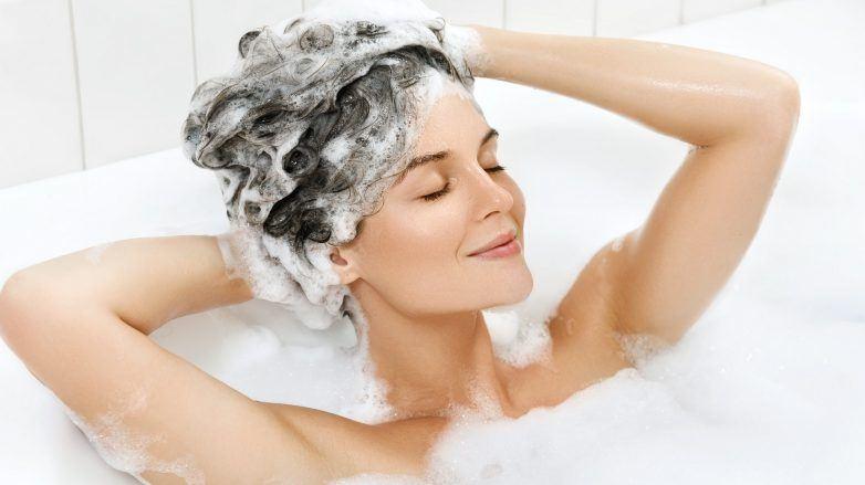 Mujer en una tina realizando la higiene del cabello