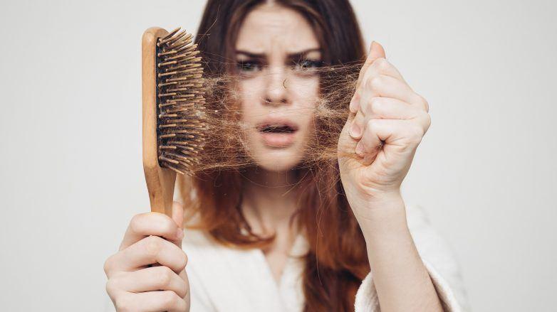 Mujer sorprendida limpiando un cepillo lleno de cabellos que se cayeron por estrés