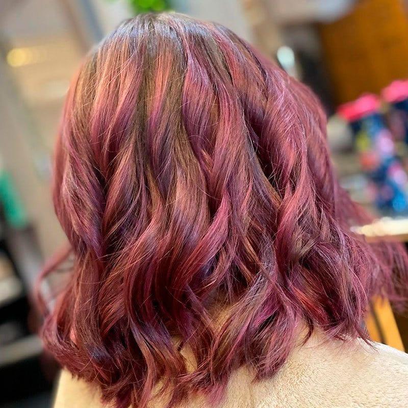 Mujer con cabello chocolate malva rosado corto ondulado