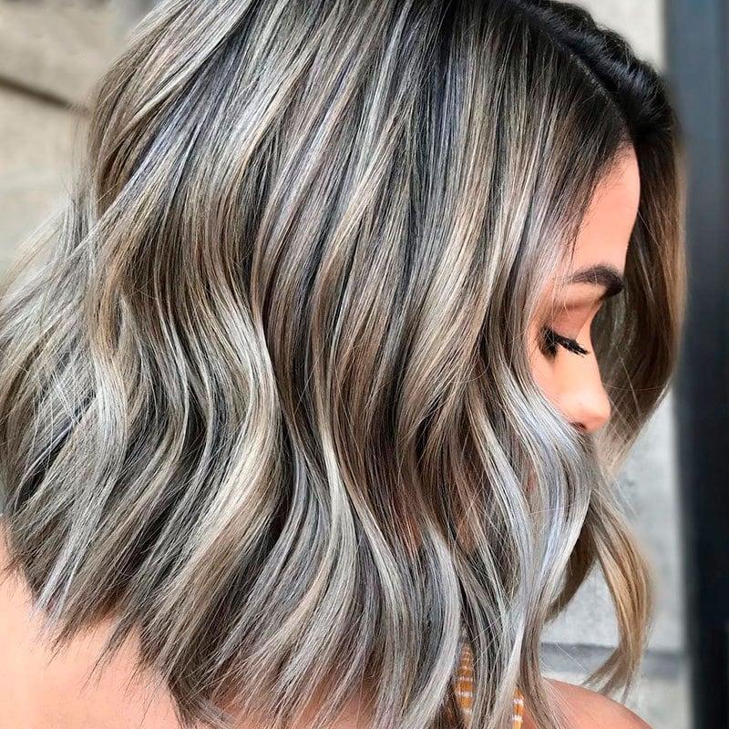 Mujer con mechas platinadas en cabello corto negro
