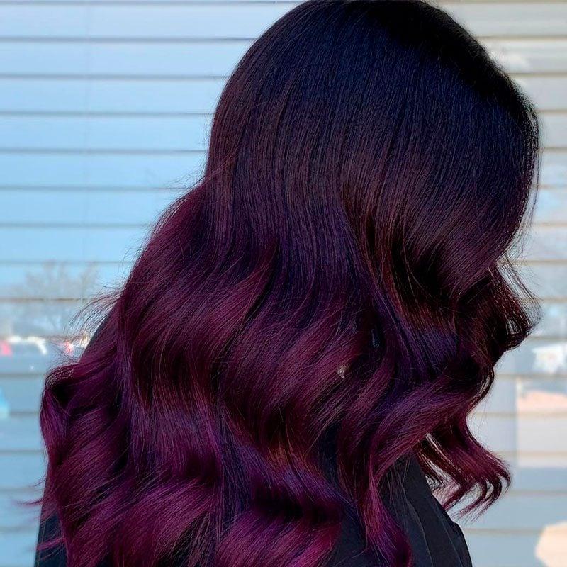 Mujer con cabello color ciruela largo ondulado