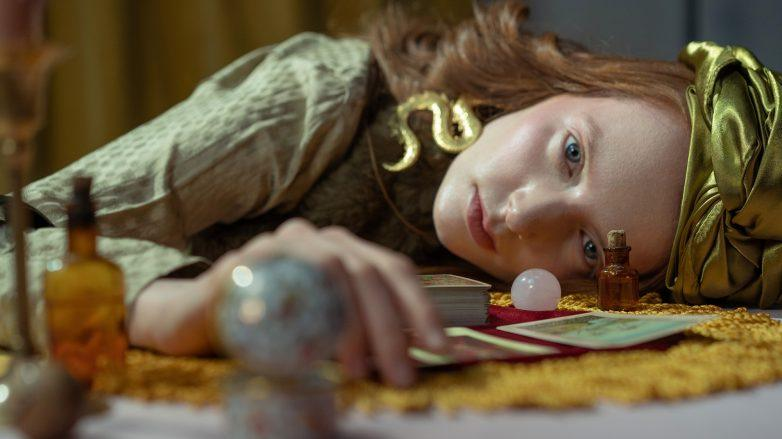 Mujer vidente recargada sobre la mesa con artilugios de brujería