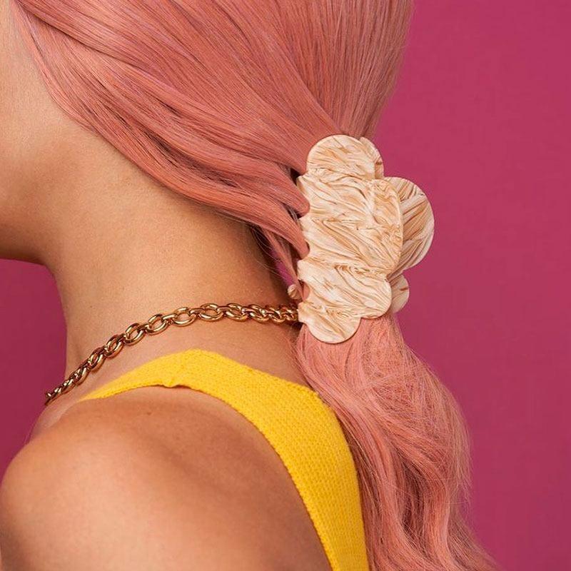 Peinado de coleta baja con pinzas, mujer con cabello rosa peinada con una pinza
