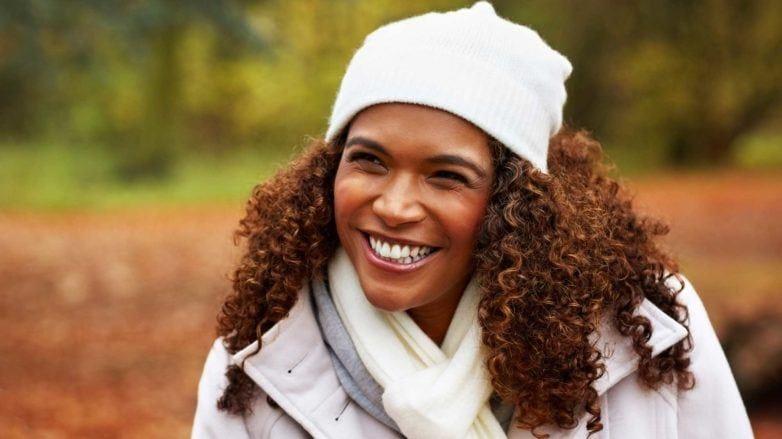 como cuidar do cabelo no frio: modelo com cabelo crespo e touca