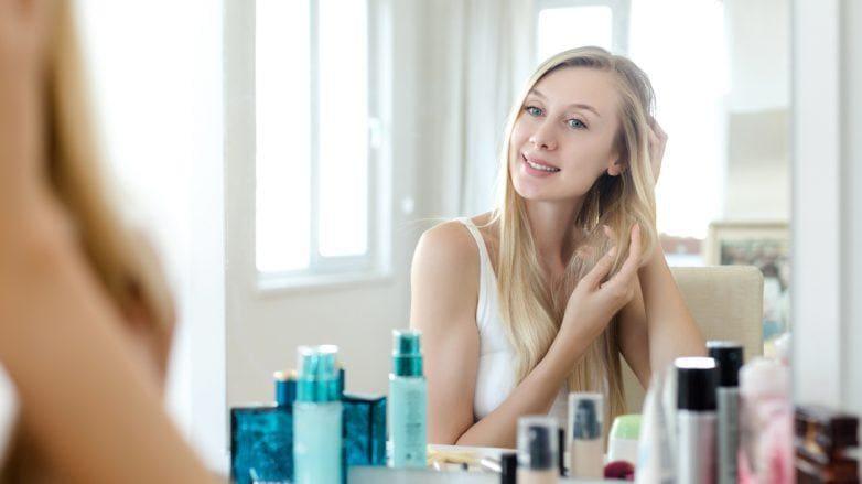 mulher com frizz no cabelo se olhando no espelho
