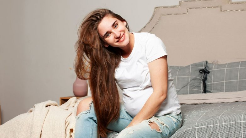 mulher com cabelo longo sorrindo sentada na cama