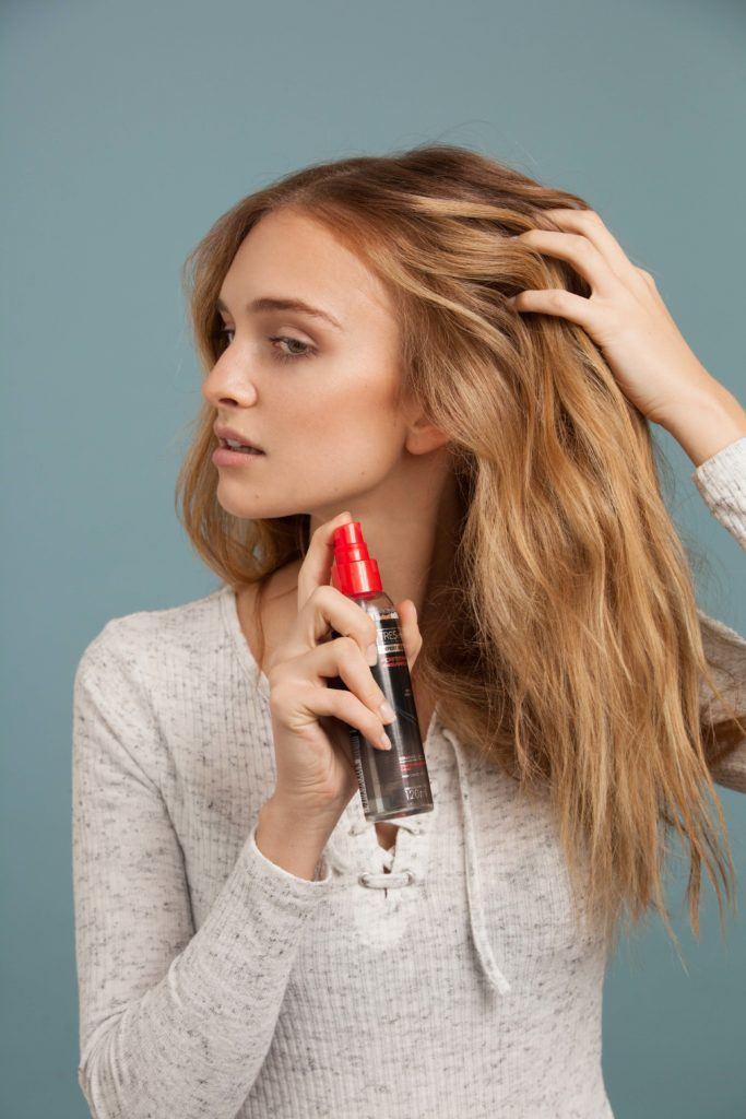 Mulher com cabelo loiro e longo passa texturizador nos fios e mostra como criar um look com efeito praia usando chapinha