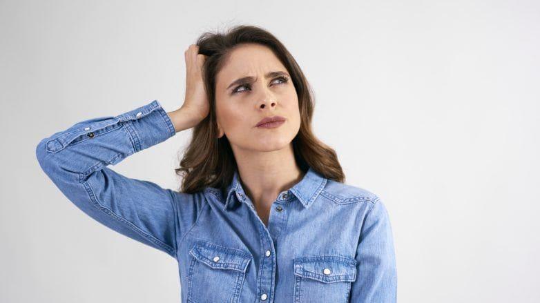 mulher com a mão no cabelo e cara de preocupada