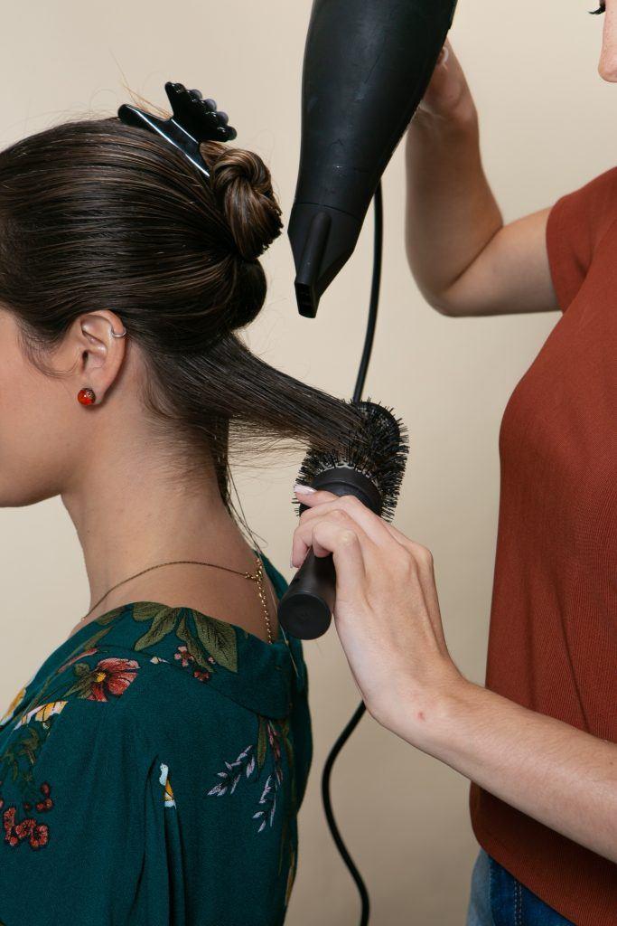 Mulher fazendo escova no cabelo da amiga