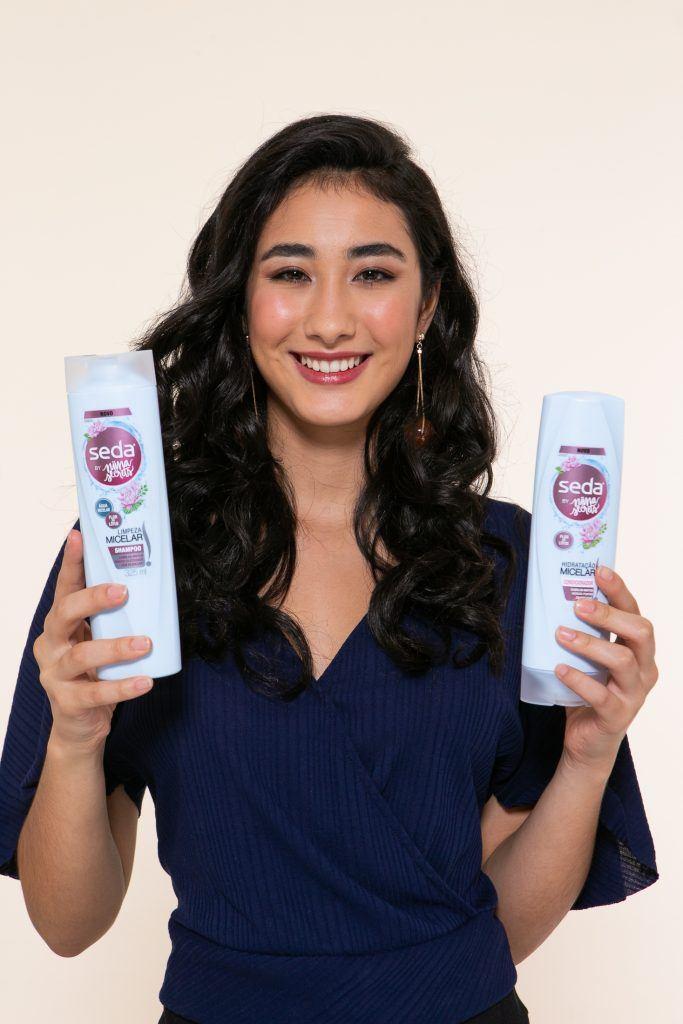 Modelo segurando shampoo e condicionador