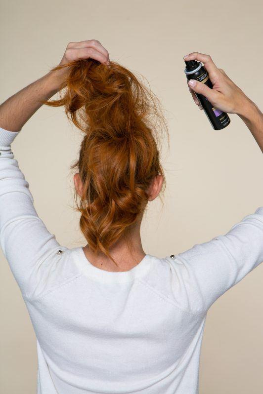 Modelo aplicando shampoo seco no rabo de cavalo