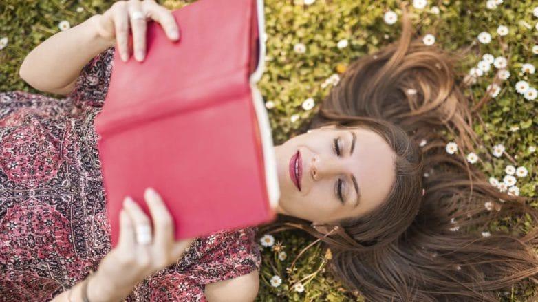 Mulher com cabelo ralo posa com livro