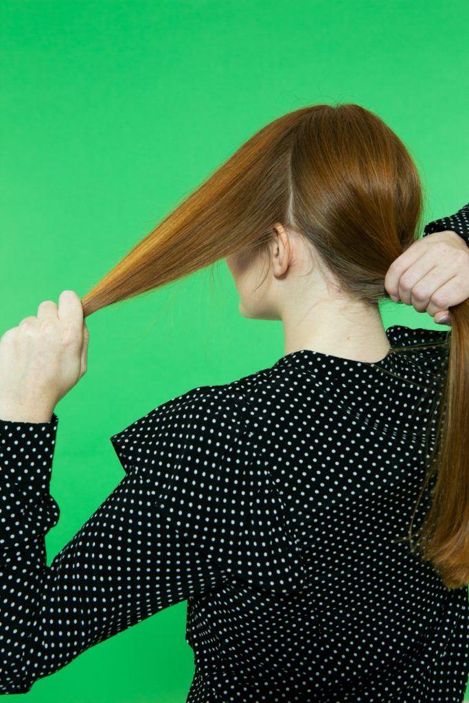 Modelo divide o cabelo no passo a passo para fazer coque chignon