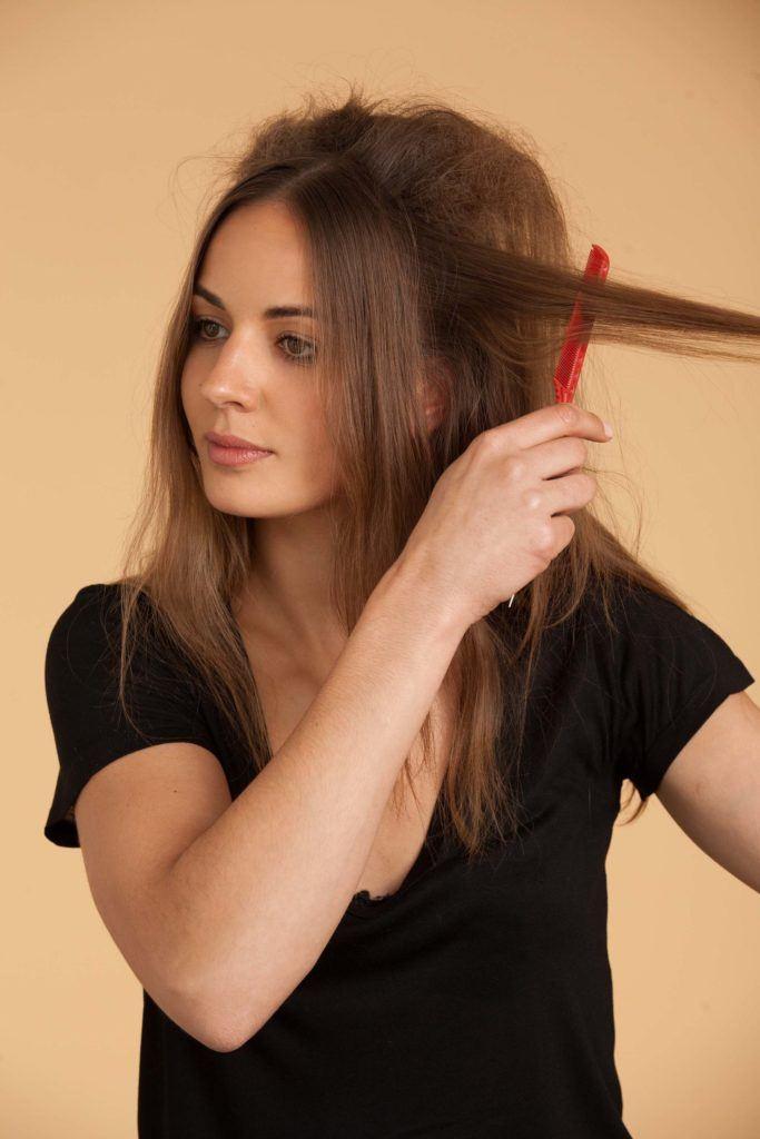 Mulher com pente fazendo coque colmeia