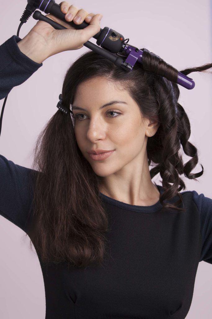 Mulher com cabelos pretos usando babyliss