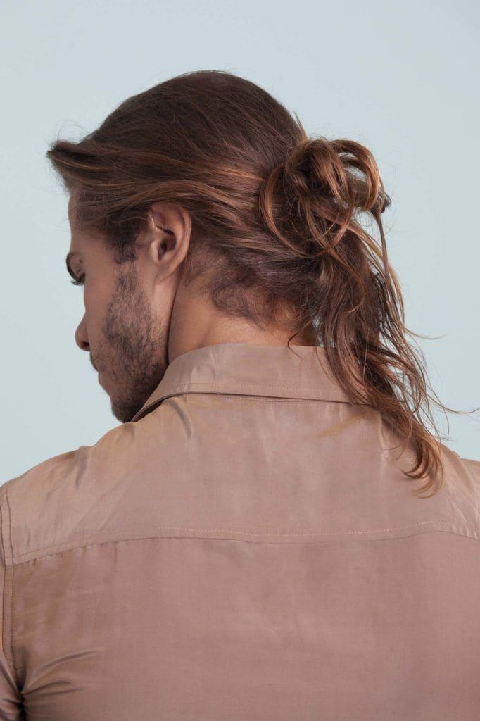 Homem com cabelos lisos e coque