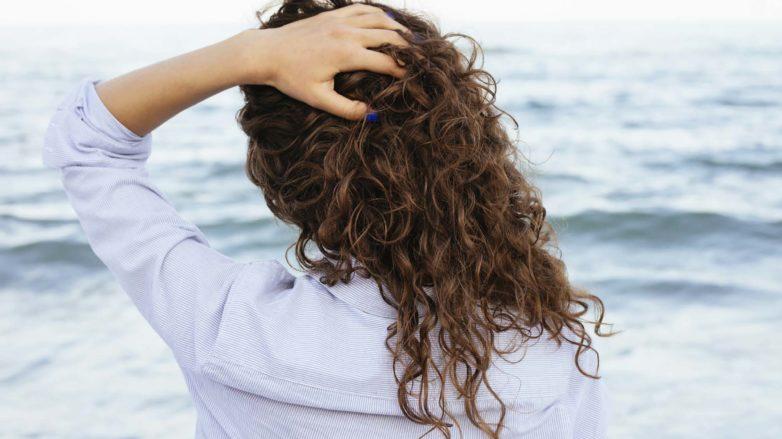 mulher de costas com cabelo cacheado