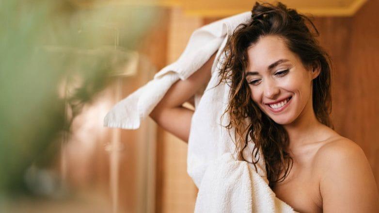Modelo secando os cabelos molhados com toalha após o banho